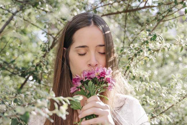 Woman smelling fresh pink flowers while standing in amidst tree park at springtime