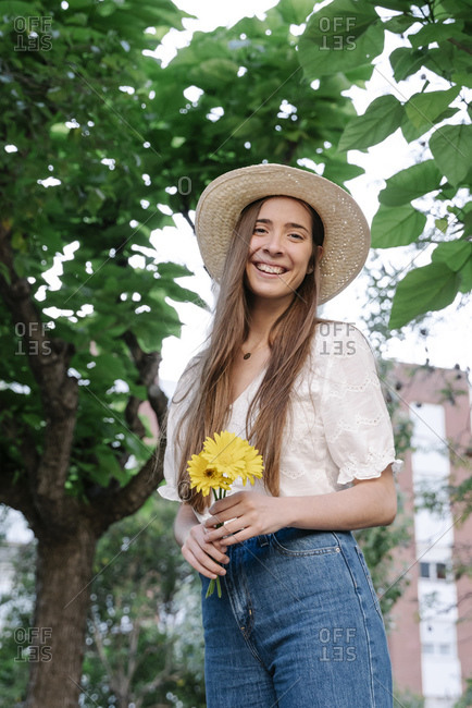 Smiling young woman wearing hat and holding yellow flowers while standing in park