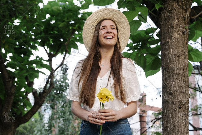 Smiling woman looking away while holding yellow flowers in public park during springtime