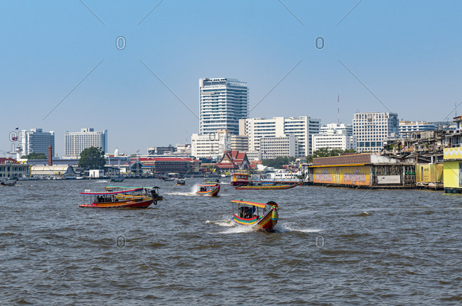 January 31, 2020: Thailand- Bangkok- Ferries on Chao Phraya river with city skyline in background