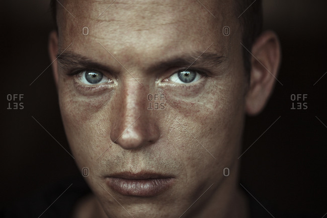 Close-up of man with gray eyes against wall
