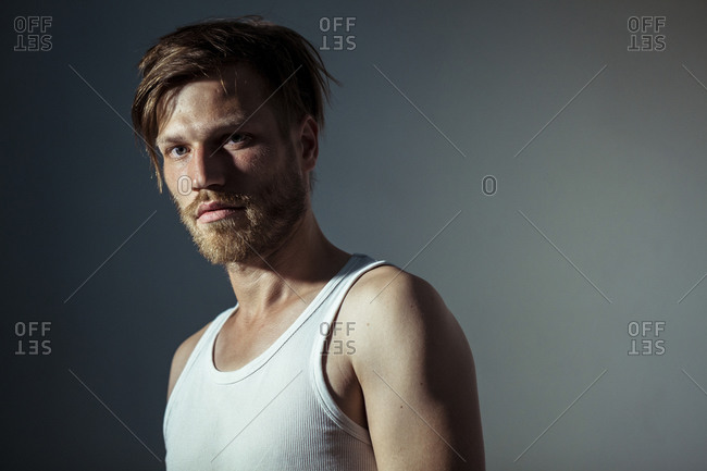 Handsome man wearing vest standing against gray background