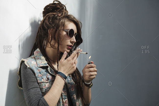 Rastafarian woman lighting cigarette against wall