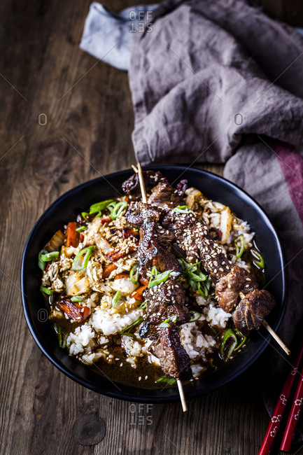 Bowl of ready-to-eat teriyaki rice with Chinese cabbage and grilled beef skewers