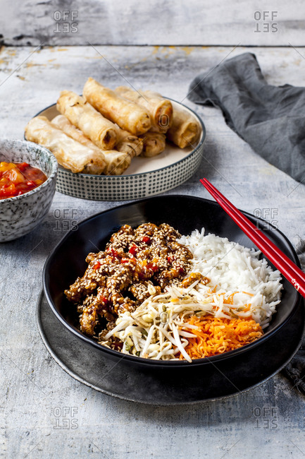 Bowl of fried sesame beef- salad and rice with dipping sauce and spring rolls in background