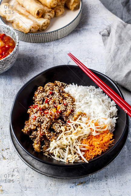 Bowl of fried sesame beef with salad and rice