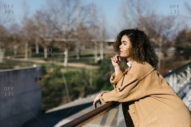 Thoughtful woman leaning on railing while looking away during sunny day