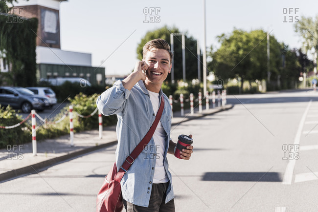 Smiling young man talking on mobile phone while crossing street in city