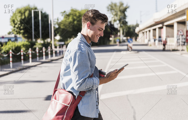 Smiling young man using mobile phone while walking on street in city