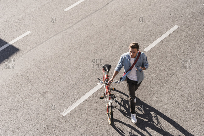 Young man crossing street with bicycle in city