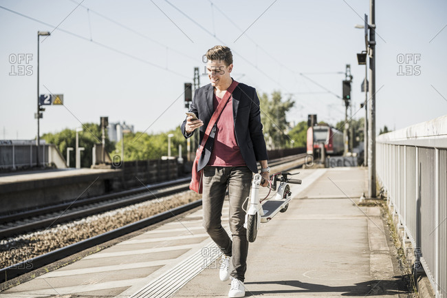 Man with push scooter using mobile phone while walking on railroad station platform