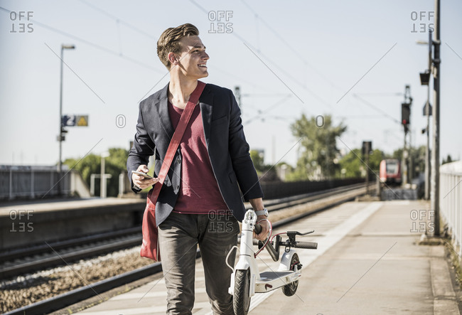 Smiling man with push scooter looking away while walking on railroad station platform