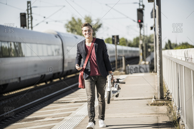 Smiling young man carrying push scooter while walking on railroad station platform