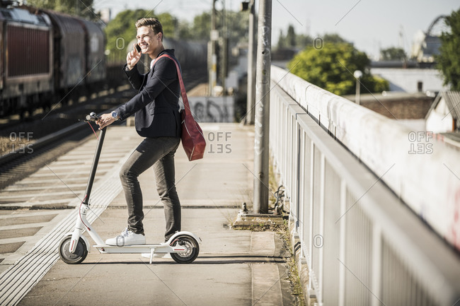 Young man talking on mobile phone while standing with push scooter at railroad station platform