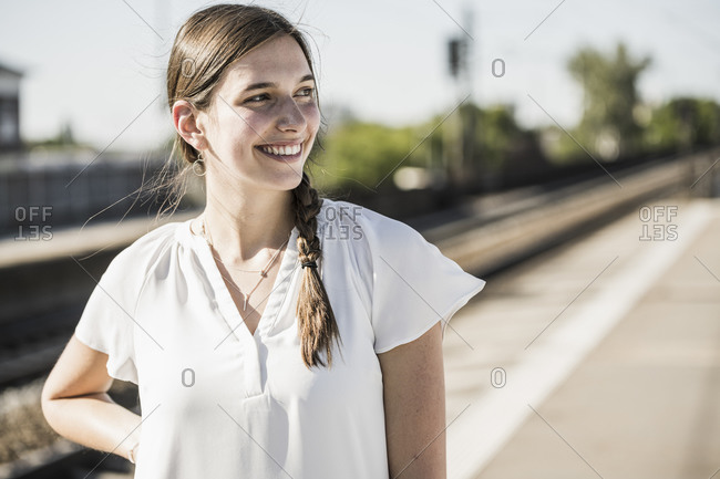 Smiling woman looking away while standing on railroad station platform