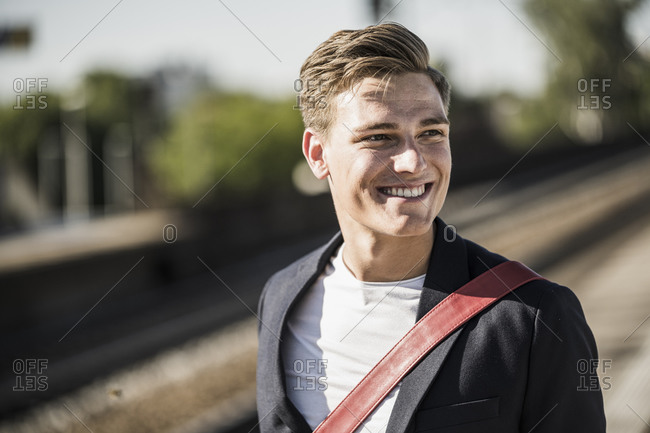 Smiling handsome young man looking away while standing at railroad station