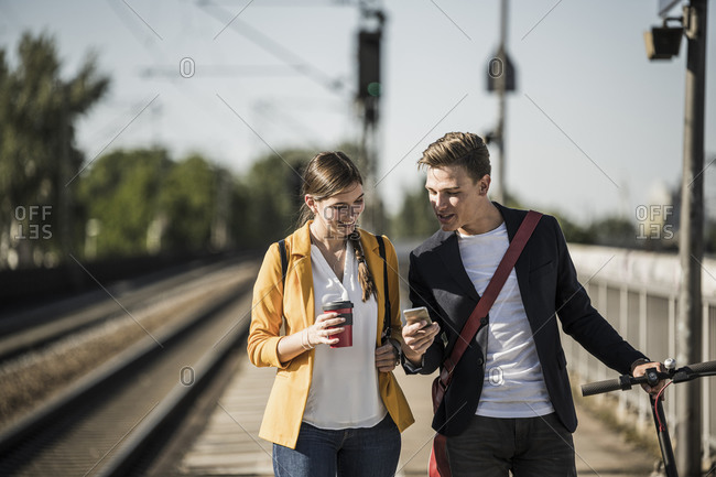 Young man showing smart phone to female friend while walking on railroad station platform
