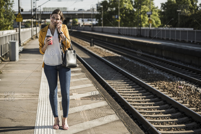 Smiling woman talking on mobile phone while standing on railroad station platform