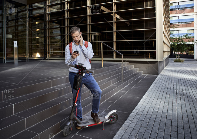 Businessman texting through phone while standing with electric scooter against staircase