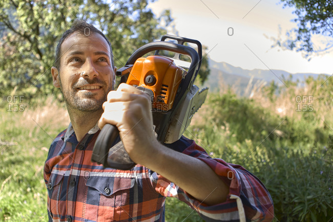 Smiling male lumberjack carrying electric saw on shoulder in forest