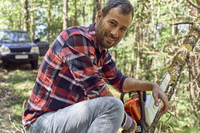 Smiling lumberjack holding chainsaw on branch in forest