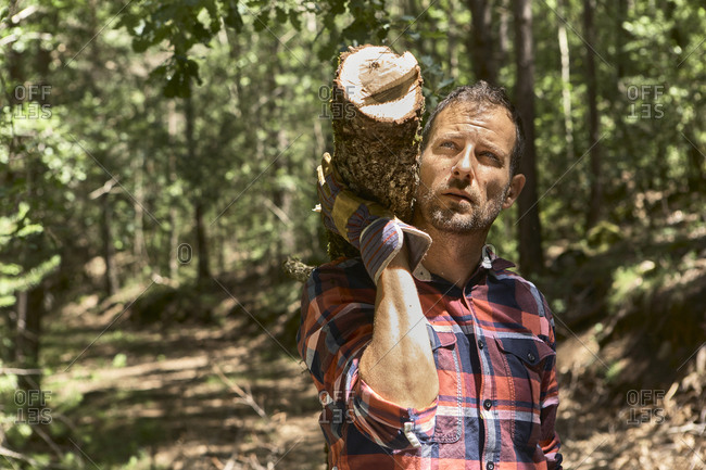 Thoughtful woodsman carrying log on shoulder while looking away in forest