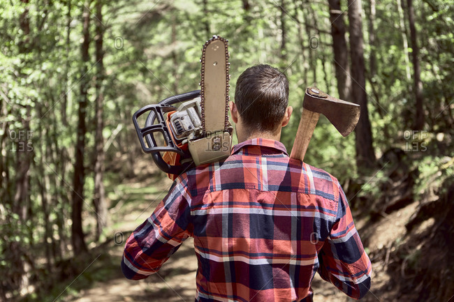 Lumberjack with chainsaw and axe walking in forest