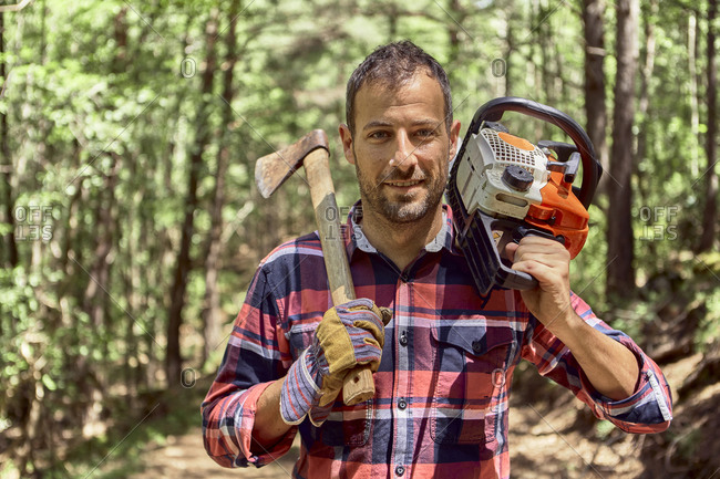 Smiling lumberjack standing with axe and chainsaw in forest