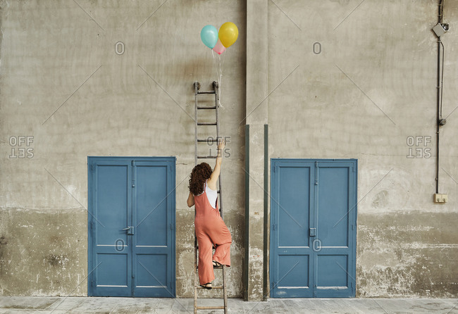 Woman climbing ladder leaning on wall while reaching for colorful helium balloons