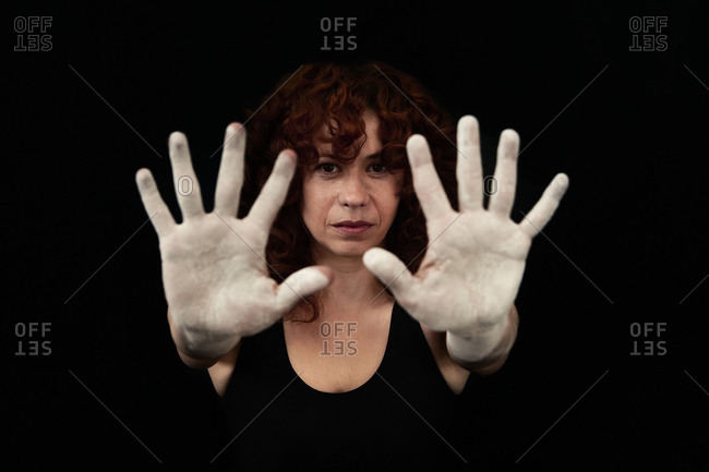 Close-up of women hands covered with white dust standing against black background