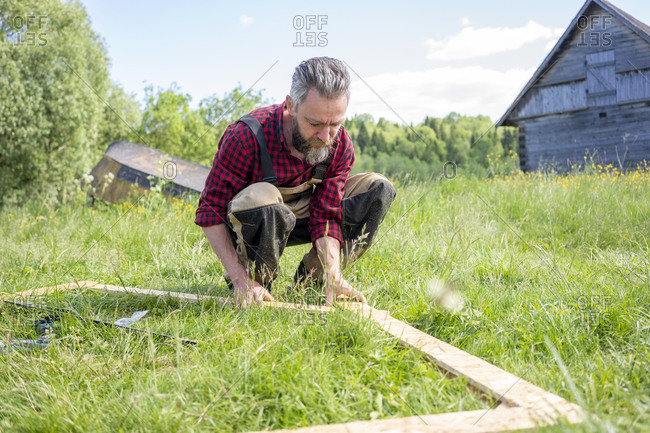 Carpenter crouching while positioning planks on grass