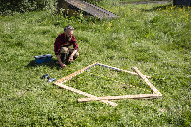 Carpenter crouching while measuring planks for playhouse on grass