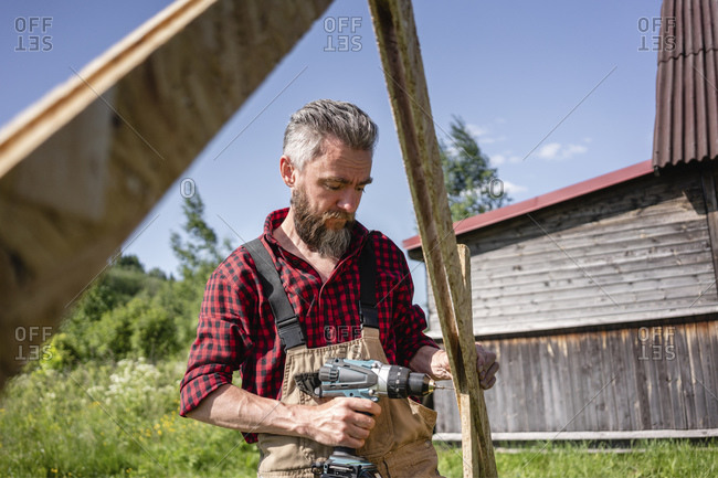 Carpenter man drilling with power tool while making playhouse