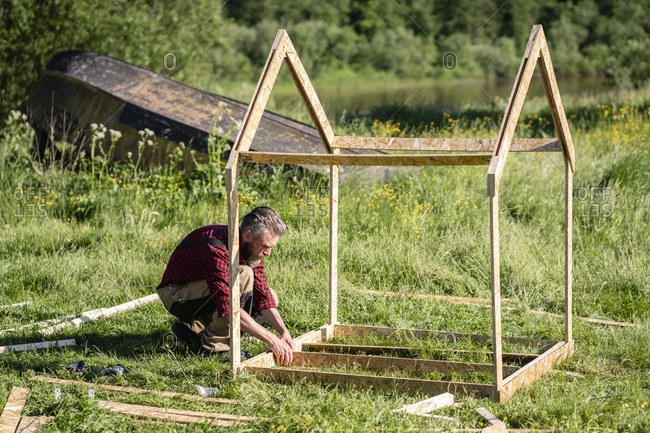 Carpenter working on building playhouse for children