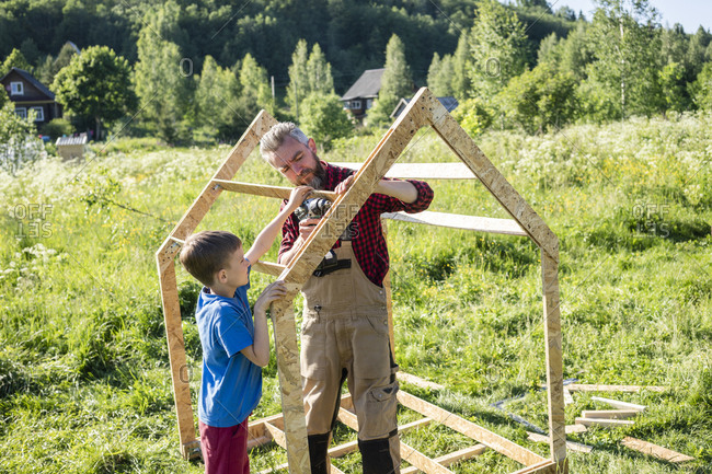 Boy helping carpenter to make playhouse on sunny day