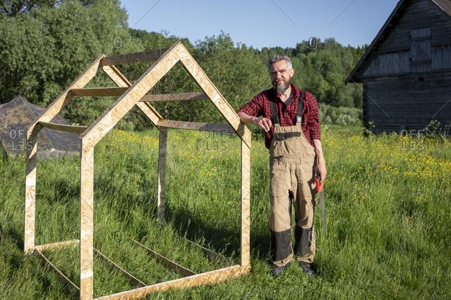 Carpenter standing wooden playhouse frame on grass