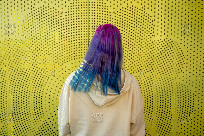Rear view of young woman with dyed hair in front of yellow wall