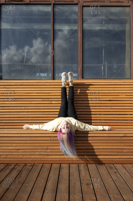 Young woman with dyed hair lying on wooden bench