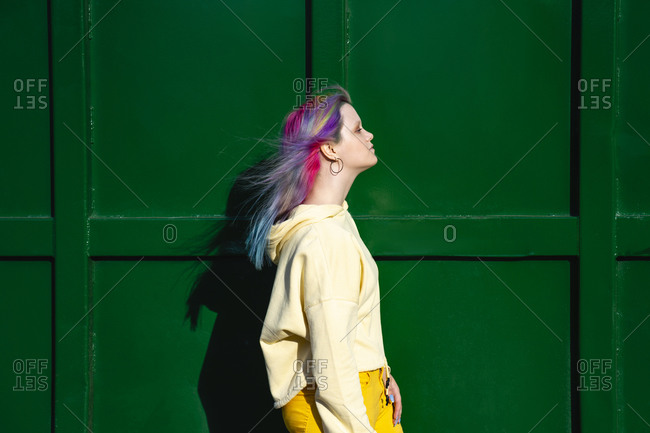 Portrait of young woman with dyed hair in front of green container