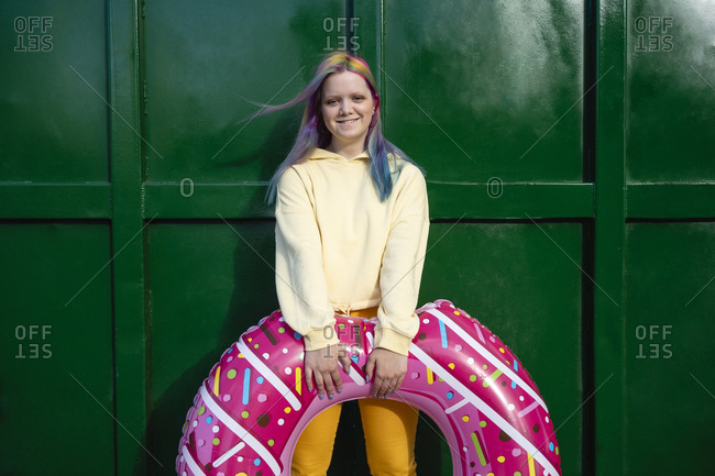 Young woman with dyed hair and floating tire in front of green container