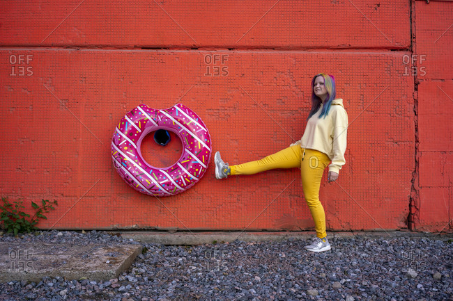 Young woman with dyed hair and floating tire hanging on red wall