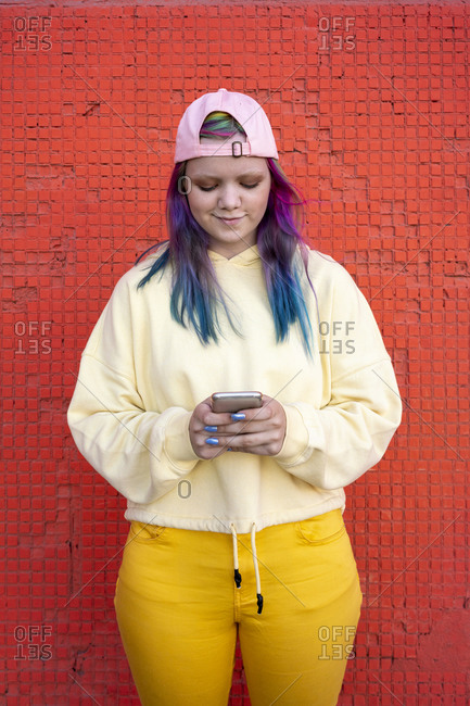Portrait of young woman with dyed hair using smartphone in front of yellow wall