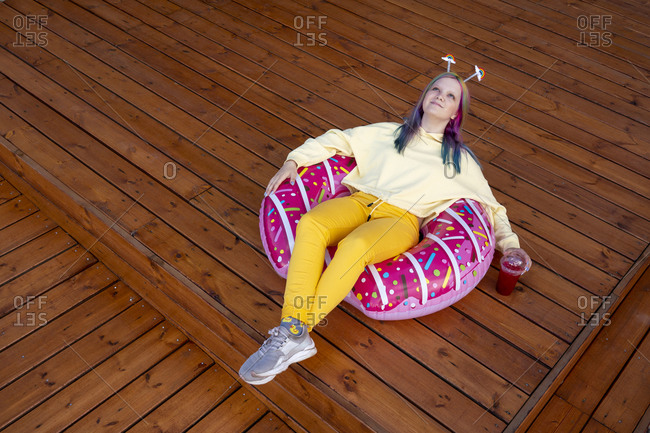 Young woman with dyed hair sitting in floating tire on wooden ground