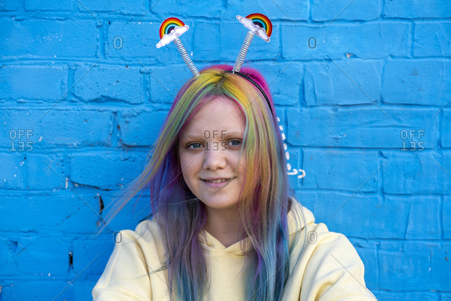 Young woman with dyed hair and rainbow headband in front of blue wall