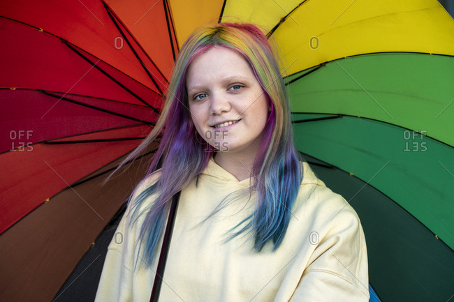 Portrait of young woman with dyed hair under umbrella