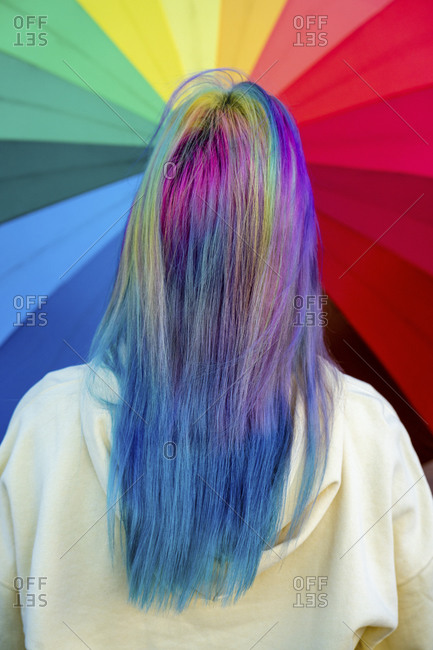 Rear view of young woman with dyed hair in front of rainbow umbrella