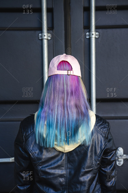 Rear view of young woman with dyed hair in front of black container
