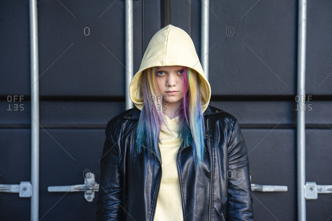 Portrait of young woman with dyed hair in front of black container