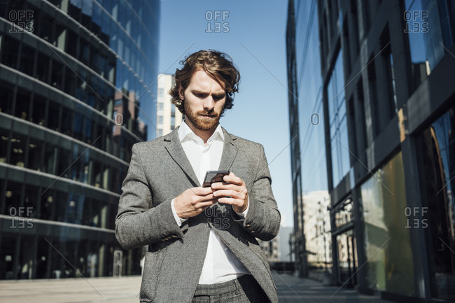 Male professional using mobile phone while standing against modern office building in downtown on sunny day