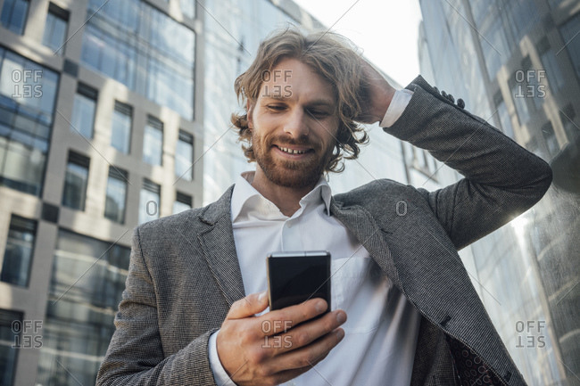 Smiling businessman with hand in hair using mobile phone against office building at downtown